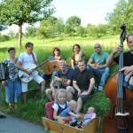 Fröhliche Familie sitzt auf der grünen Somerwiese.Sie haben Instrumente dabei und drei Kinder stehen im Vodergrund.