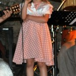 Ein kleines blondes Mädchen spricht und singt in ein Mikrophon.