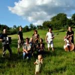 Zehn Menschen mit Instrumenten auf einer grünen Sommerwiese unter blauem Himmel. Ein Kleinkind steht im Vordergrund.
