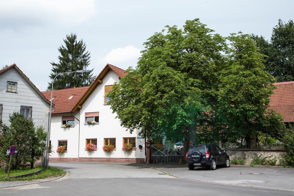 Weißes Haus mit angrenzendem Tor und großem Baum. Davor steht ein schwarzes Automobil.