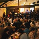 Ein voller Saal. Die Menschen essen. Im Hintergrund sitzt ein Orchester.