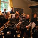 Ein Orchester spielt Blasinstrumente. Ihre Notensständer stehen im Vordergrund.