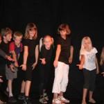 Zu sehen sind viele Kinder, welche sich vor dem Publikum verneigen.