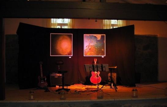 Das Bild zeigt eine Konzertbühne mit Gitarren und Verstärkern.